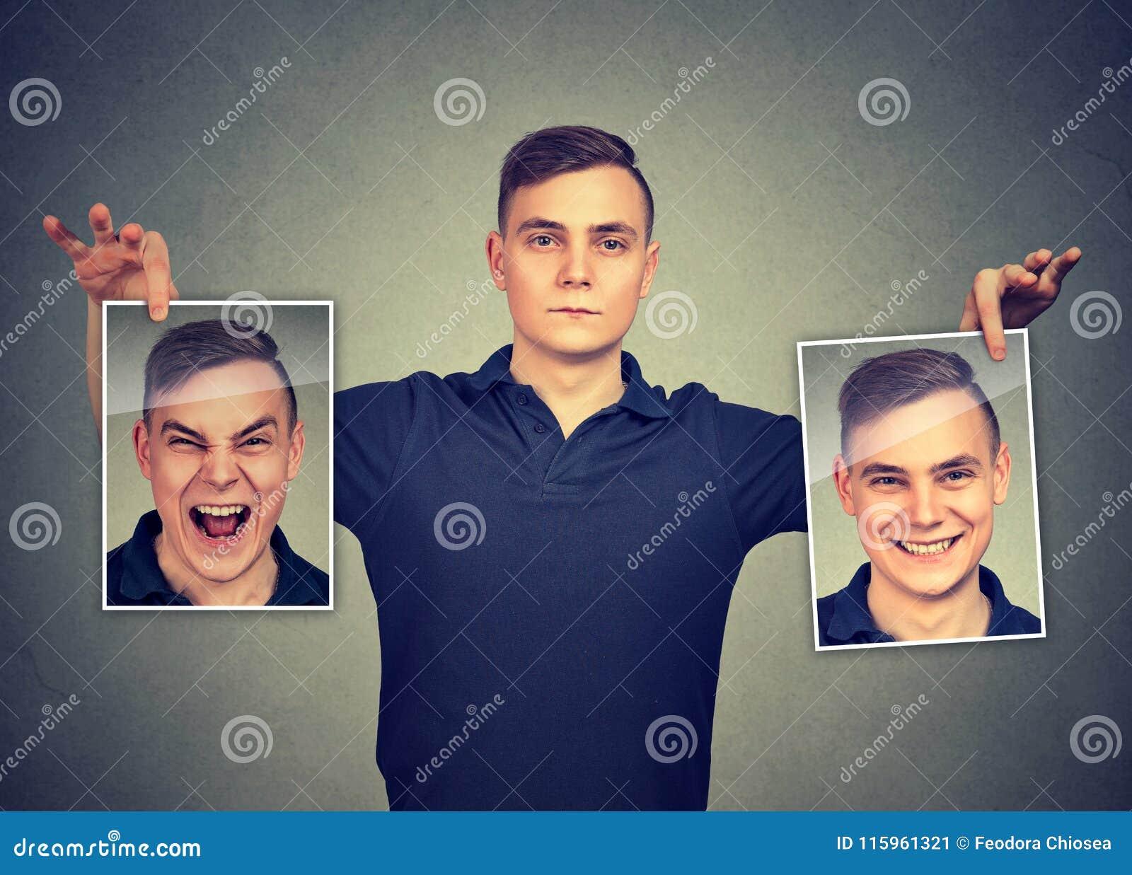 Poważny mężczyzna trzyma dwa różnej twarzy emoci maski on