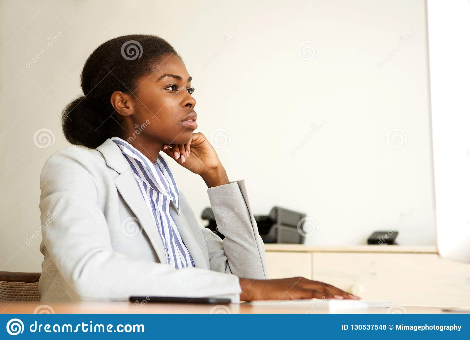 Poważny młody czarny biznesowej kobiety obsiadanie w biurowym patrzeje ekranie komputerowym