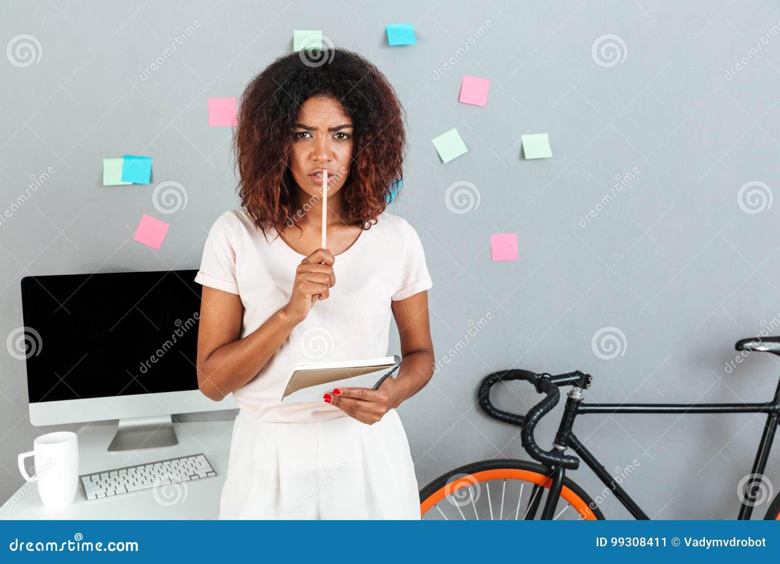 Poważny myślący młody afrykański kobiety mienie ołówkowy