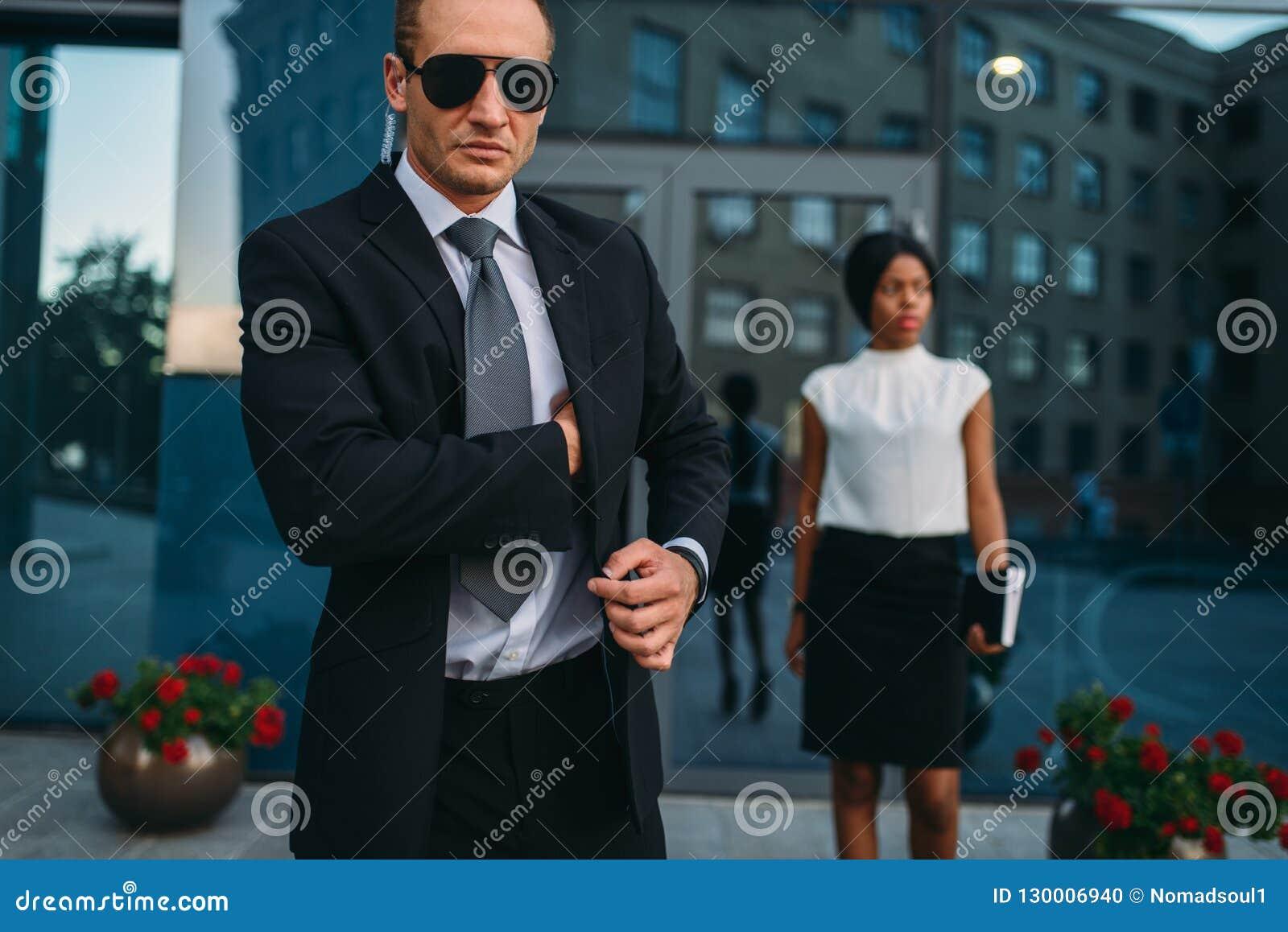 Poważny ochroniarz w kostiumu, okularach przeciwsłonecznych i earpiece,