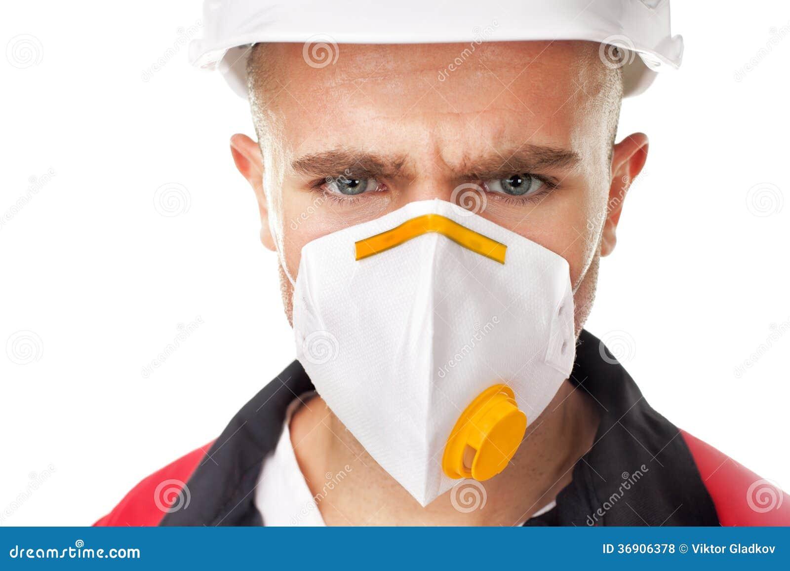 Poważny pracownik jest ubranym respirator