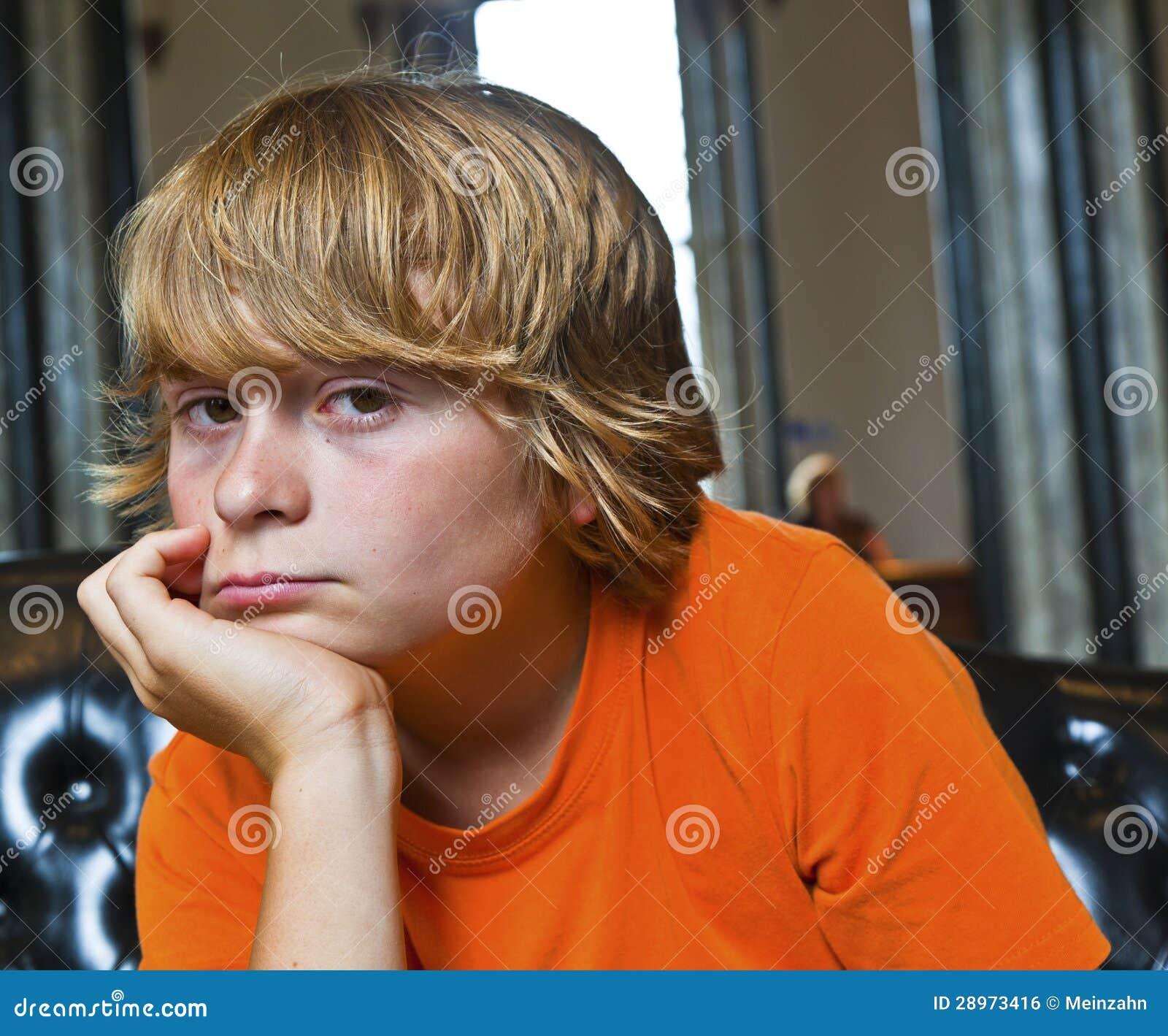 Poważny przyglądający chłopiec obsiadanie na kanapie