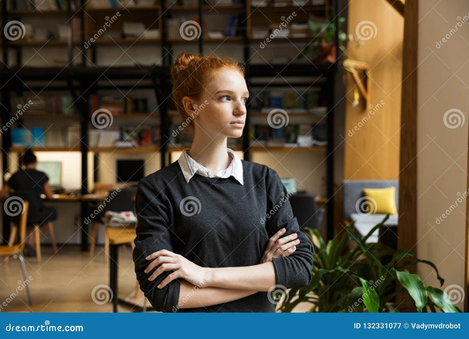 Poważny skoncentrowany rudzielec damy uczeń pozuje indoors w bibliotece