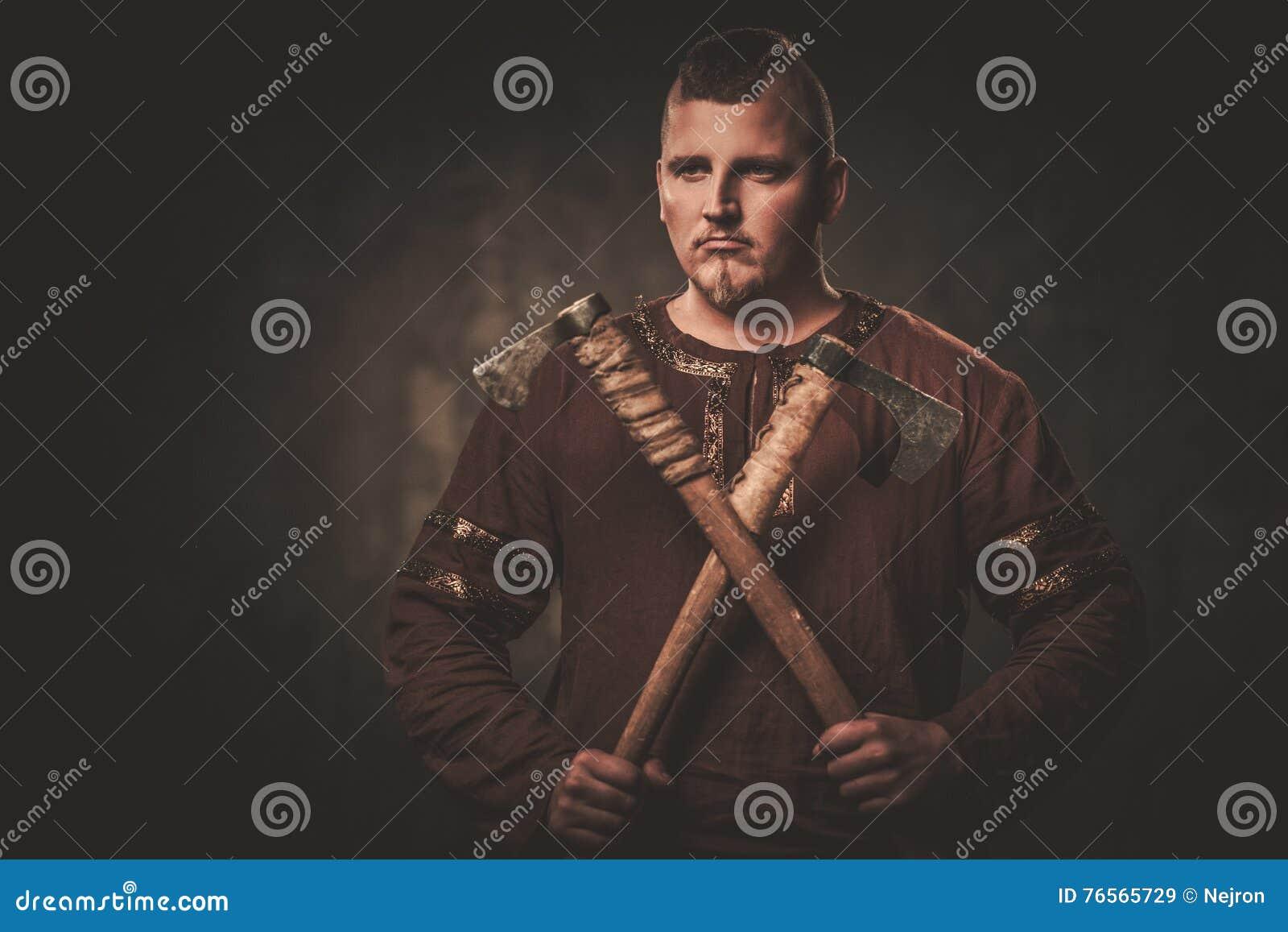 Poważny Viking z cioskami w wojownika tradycyjnych ubraniach, pozuje na ciemnym tle