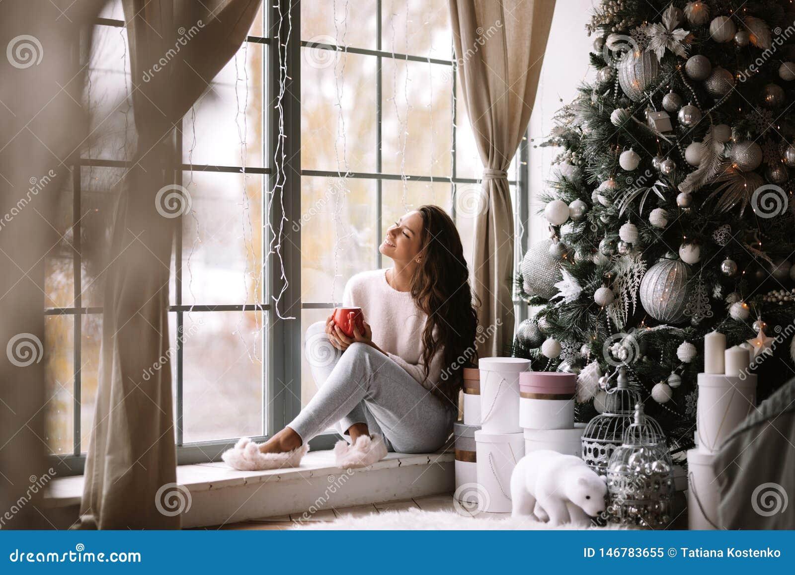 Powabna ciemnowłosa dziewczyna ubierał w spodniach, pulower i ciepli kapcie trzymają czerwonego filiżanki obsiadanie na windowsil