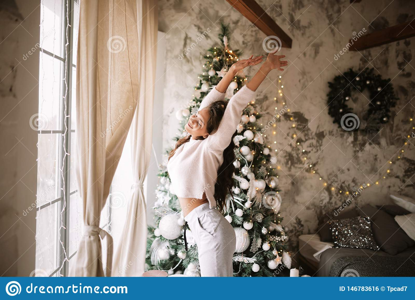 Powabna dziewczyna ubiera? w bia?ych puloweru, spod? stojakach obok nowego roku drzewa przed i rozci?gliwo?? i okno