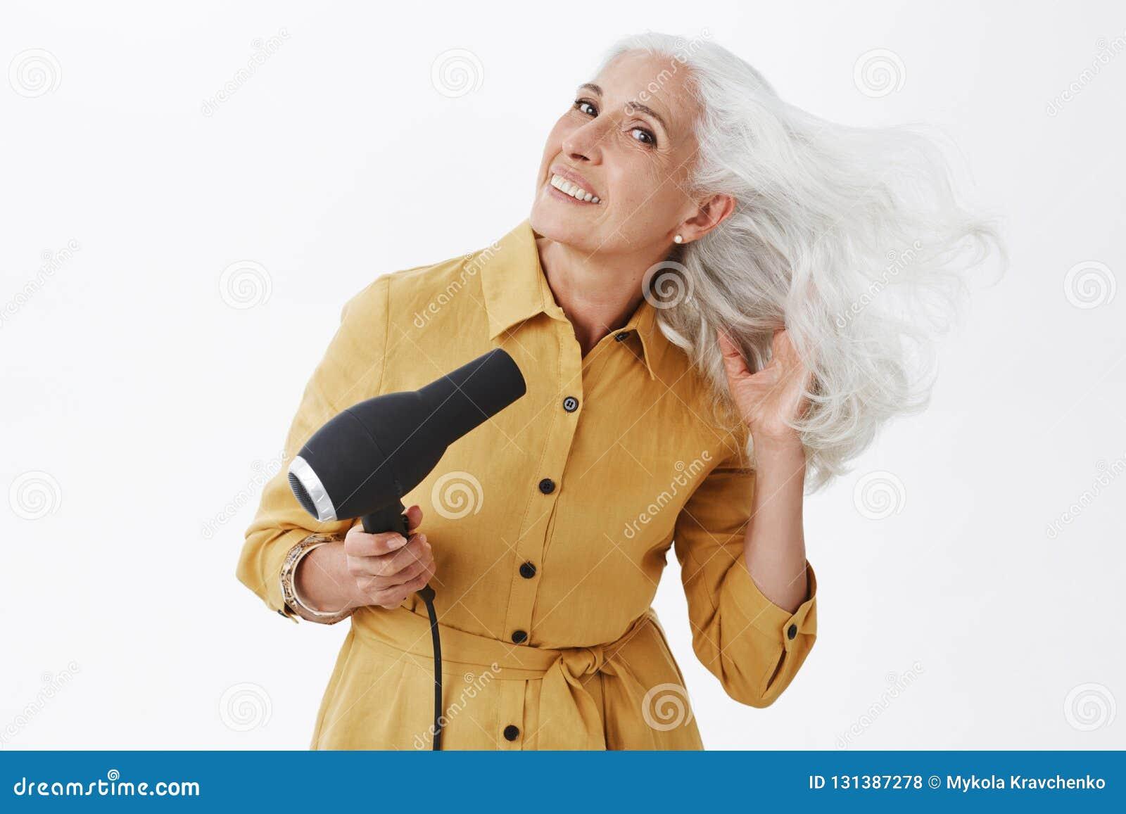 Powabna elegancka babcia z popielatą włosianą pozycją w modnym żółtym żakieta chylenia dobrze, robi ostatnim przygotowaniom iść