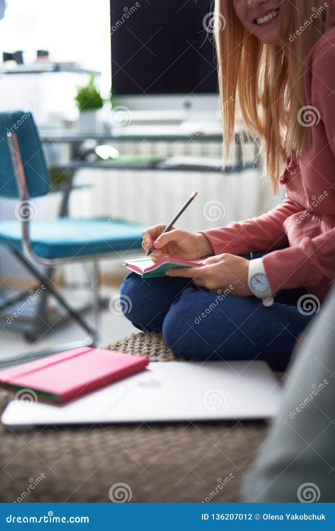 Powabna młoda dama pisze na notatniku w różowym hoodie