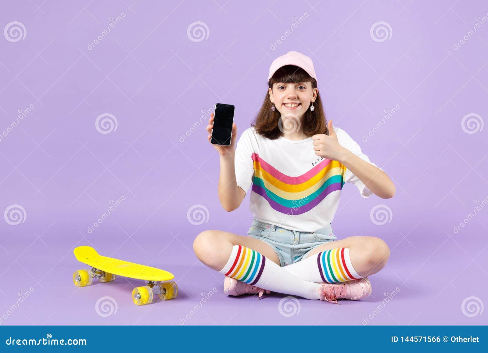 Powabna nastoletnia dziewczyna siedzi blisko deskorolka trzyma telefon kom?rkowego z puste miejsce pustym ekranem, pokazuje kciuk