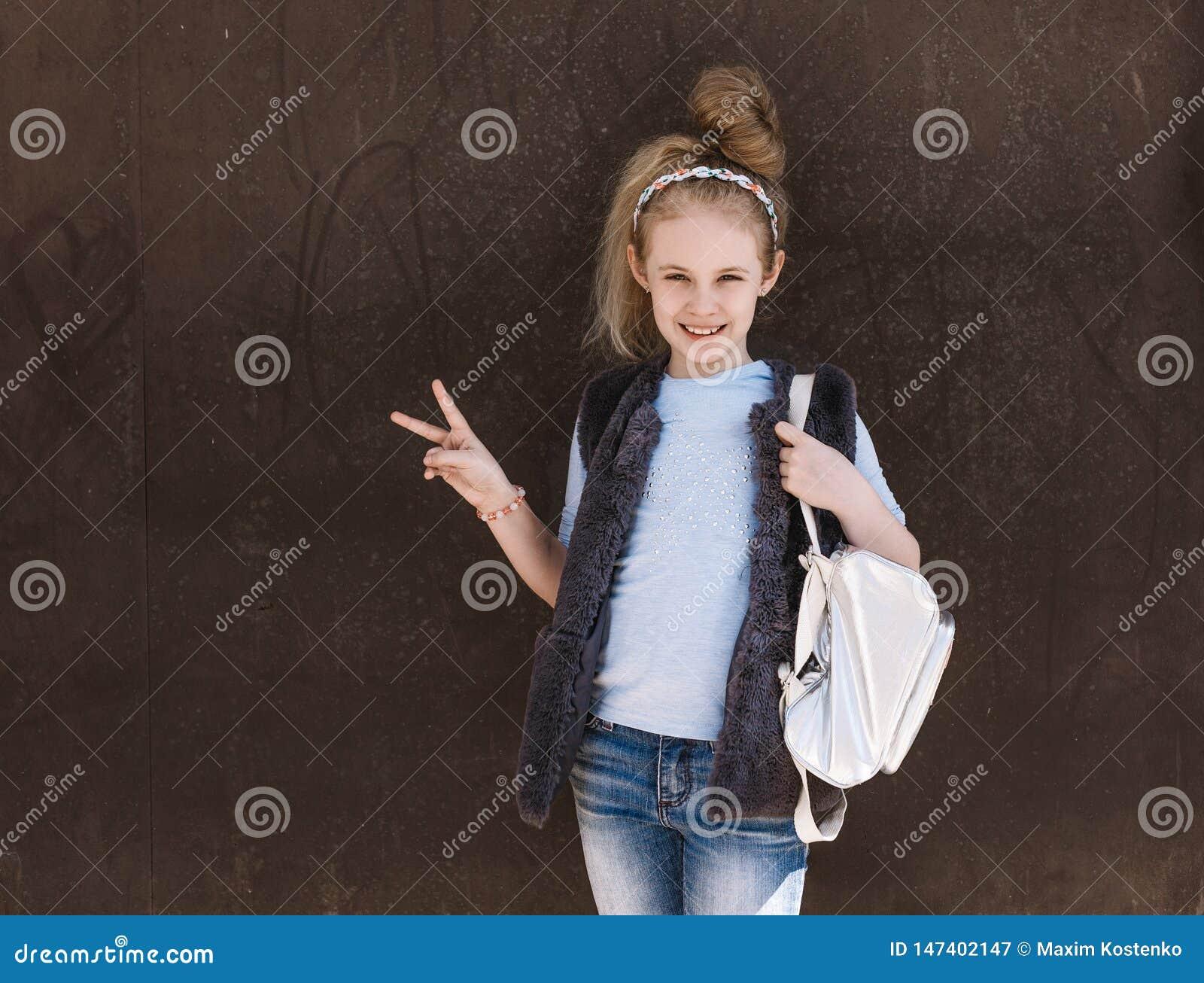 Powabna ośmioletnia dziewczyna w modnym stroju z plecak pozycją na ulicie na słonecznym dniu
