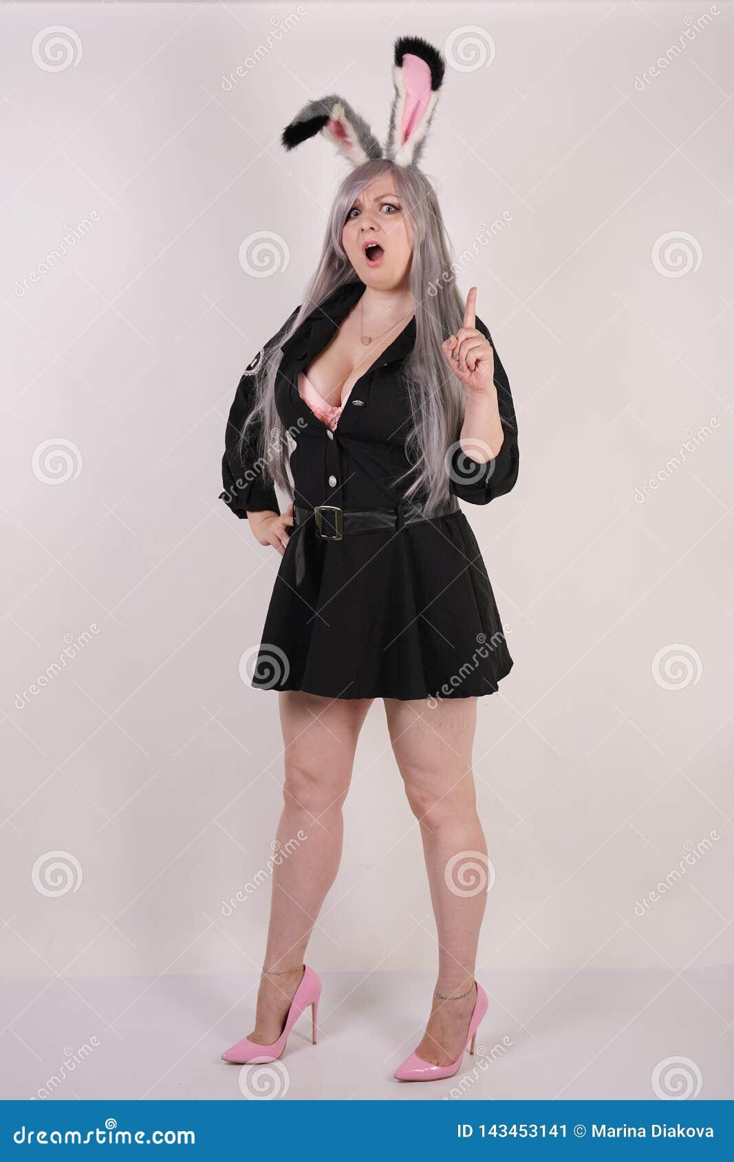 Powabna pyzata dziewczyna w milicyjnym kostiumu z cosplay królików ucho bardzo emocjonalnymi i gniewnymi na białym tle