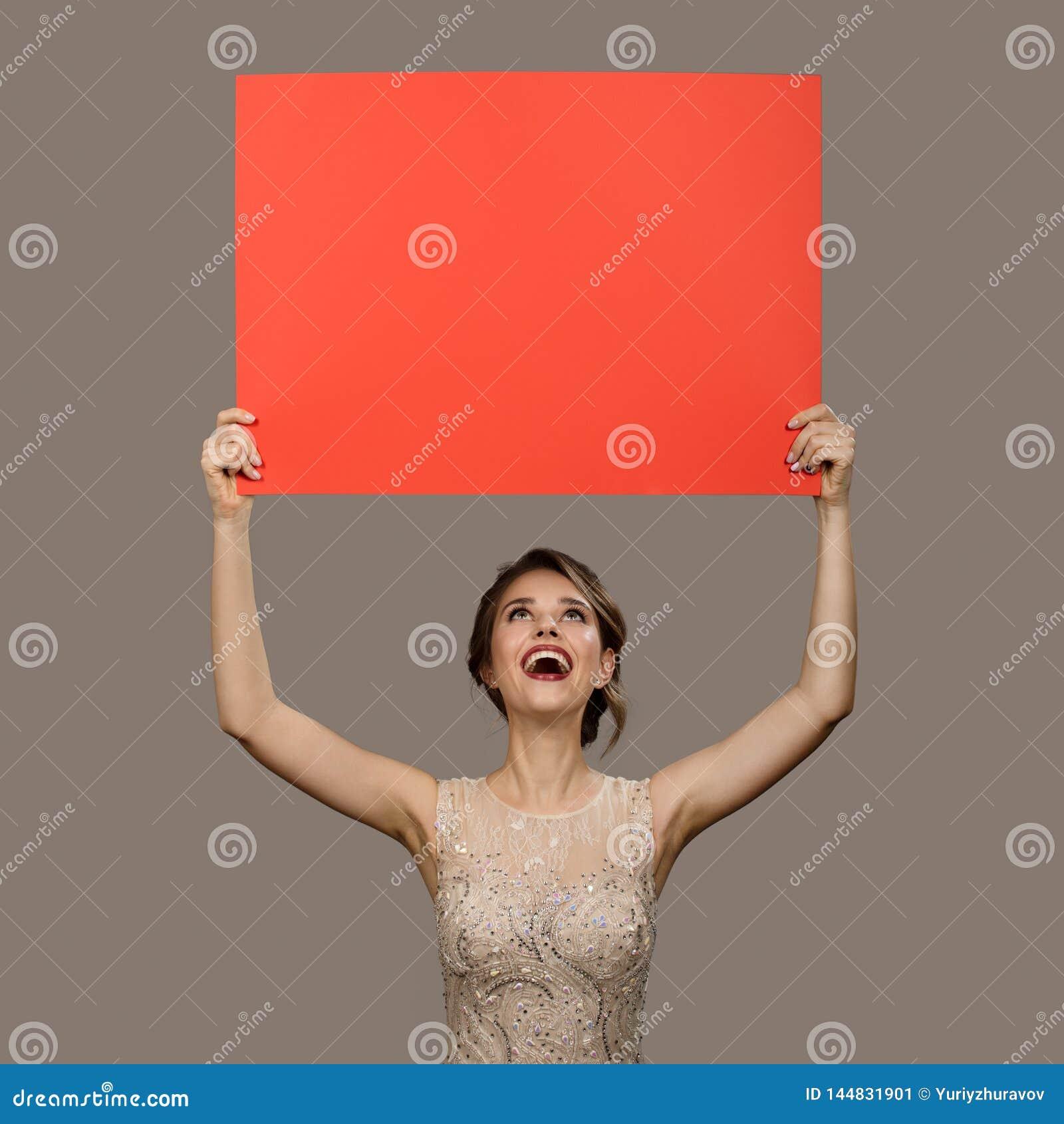 Powabna szcz??liwa kobieta trzyma du?ego czerwie? papieru pustego puste miejsce