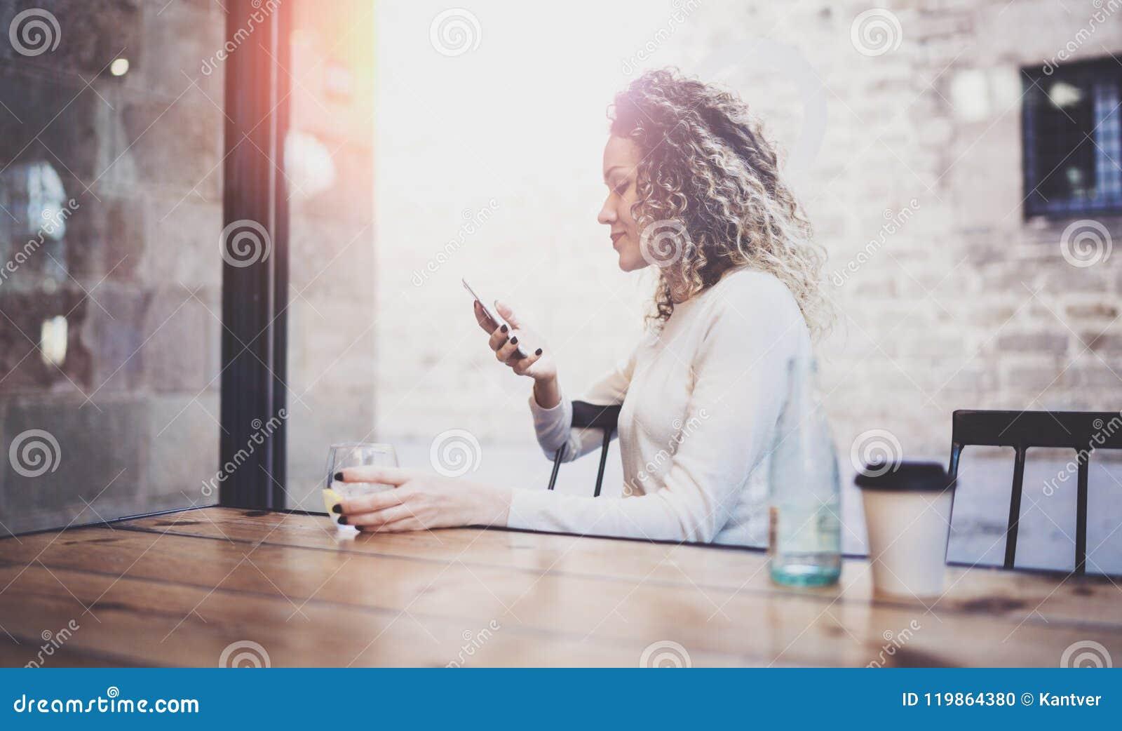 Powabnej pięknej młodej kobiety czytelniczy e-mail na telefonie komórkowym podczas spoczynkowego czasu w sklep z kawą Bokeh i rac