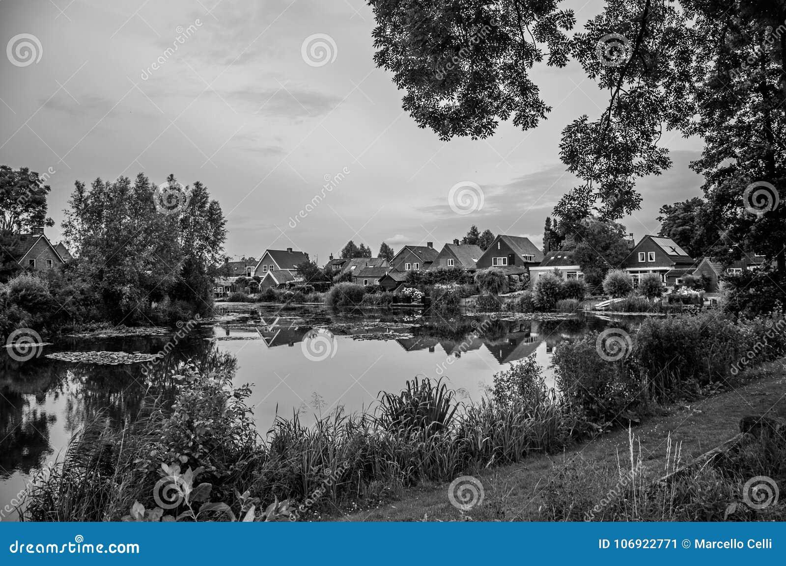 Powabny kanał obok wieśniaków domów z krzakami, gazonem i drzewami w chmurnym dniu przy Drimmelen,