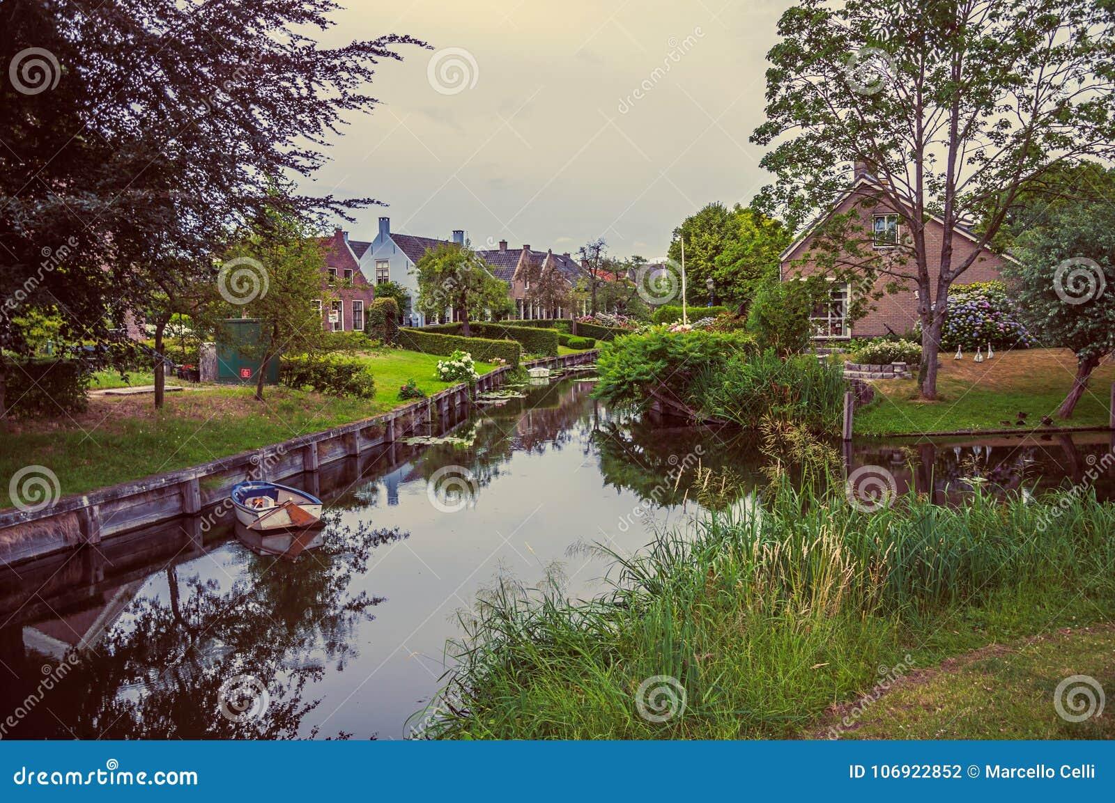 Powabny kanał obok wieśniaków domów z ogródami, drzewami i łodzią w chmurnym dniu przy Drimmelen,