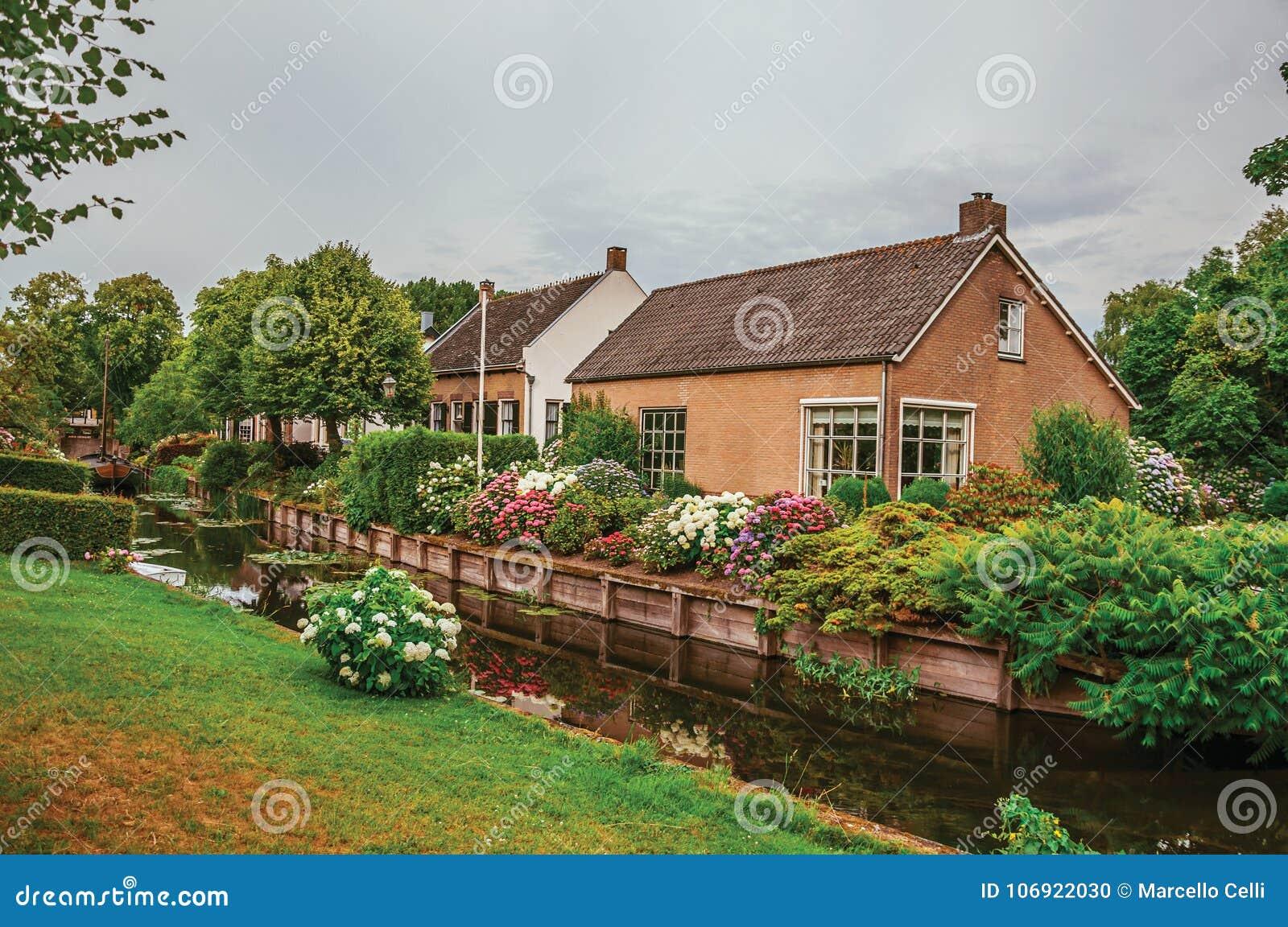 Powabny mały kanał obok wieśniaków domów z luksusowym kwiaciastym ogródem i gazonem w chmurnym dniu przy Drimmelen