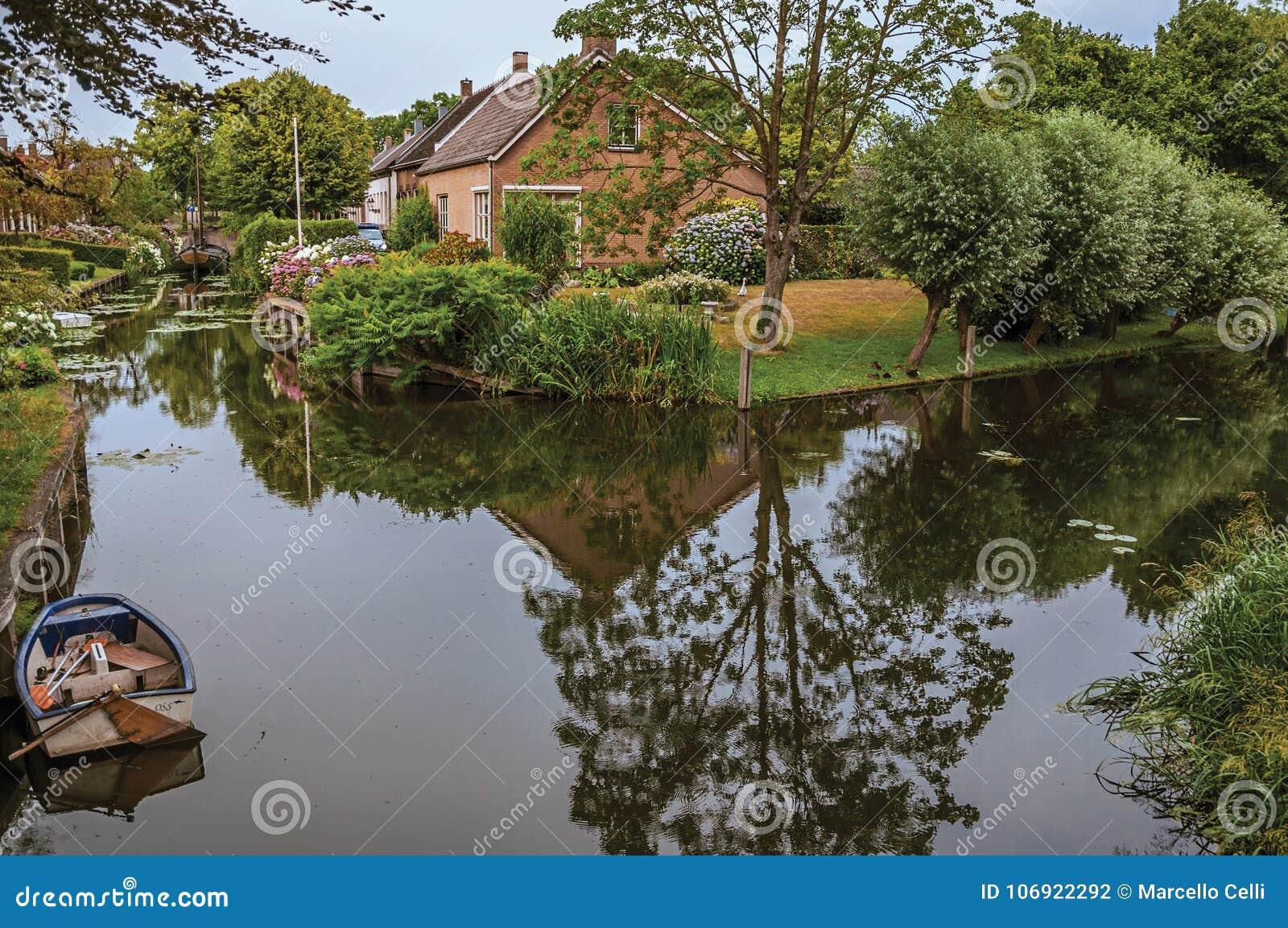 Powabny mały kanał obok wieśniaka domu z luksusowym ogródem i drzewa odbijaliśmy na wodzie w chmurnym dniu przy Drimmelen