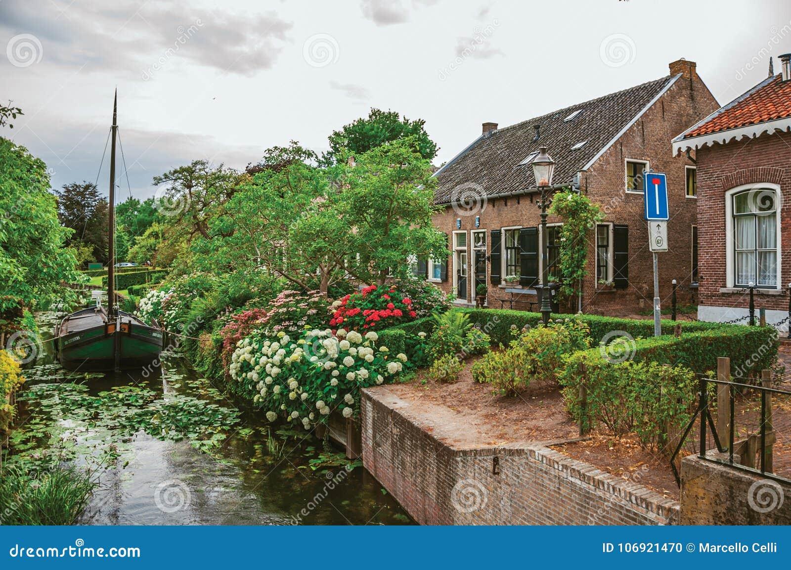 Powabny mały kanał z łodzią obok ceglanego wieśniaka domu luksusowego kwiaciastego ogródu w chmurnym dniu przy Drimmelen i