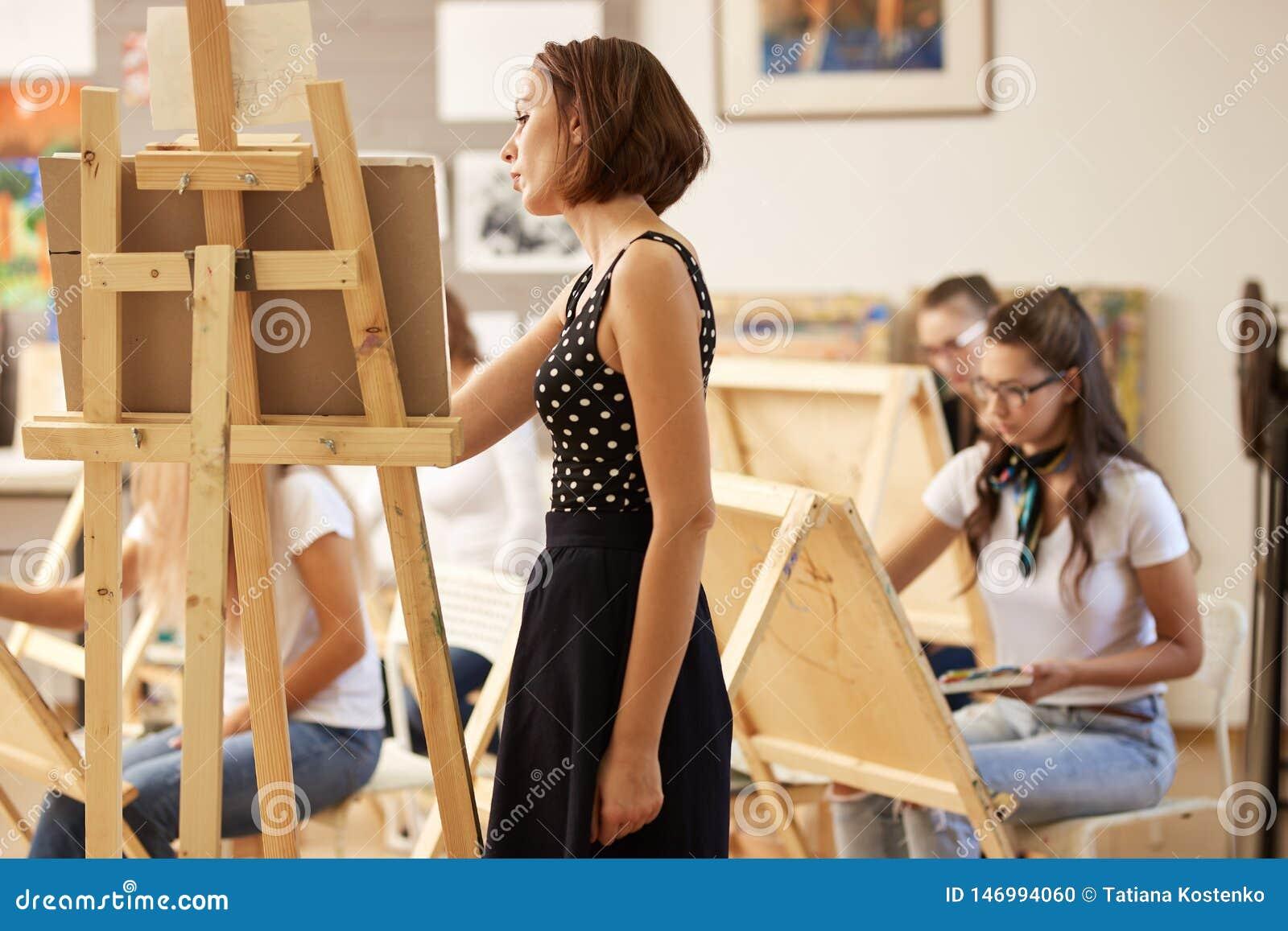 Powabny rysunkowy nauczyciel w pi?knej sukni pokazuje rysunkow? technik? przy sztalug? w sztuki studiu