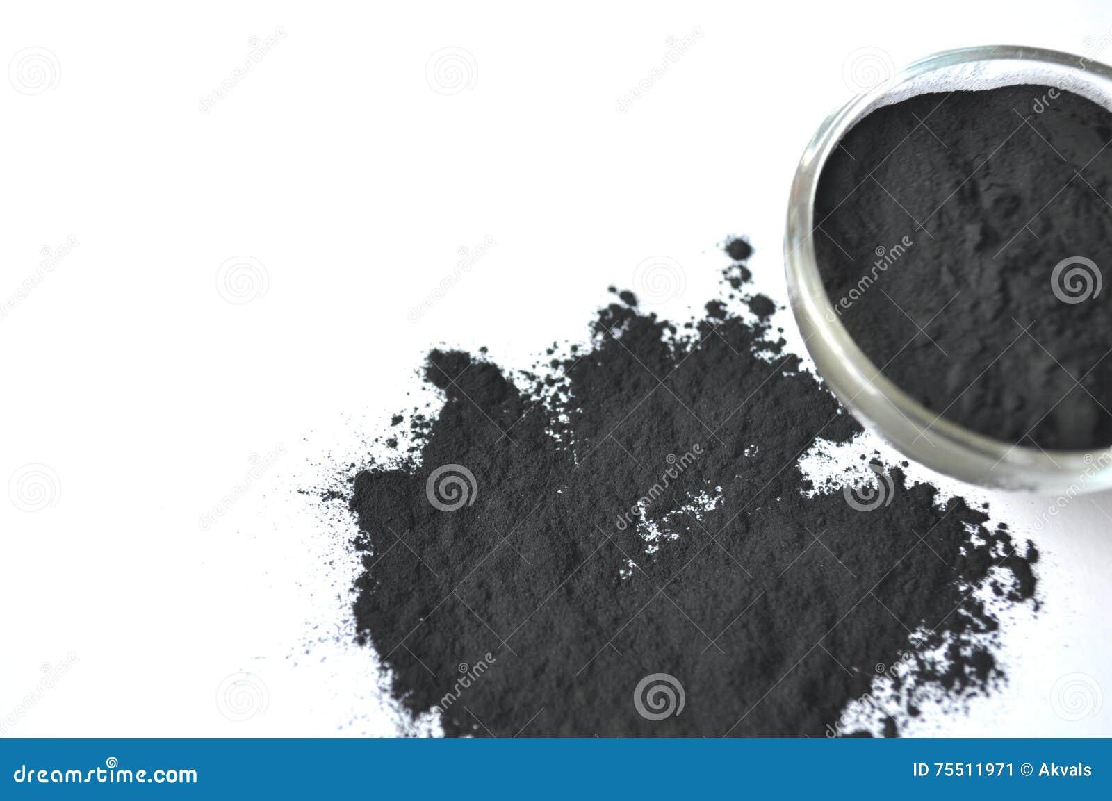 Powdered aktiverade kol i en glass bunke och som omkring strilade