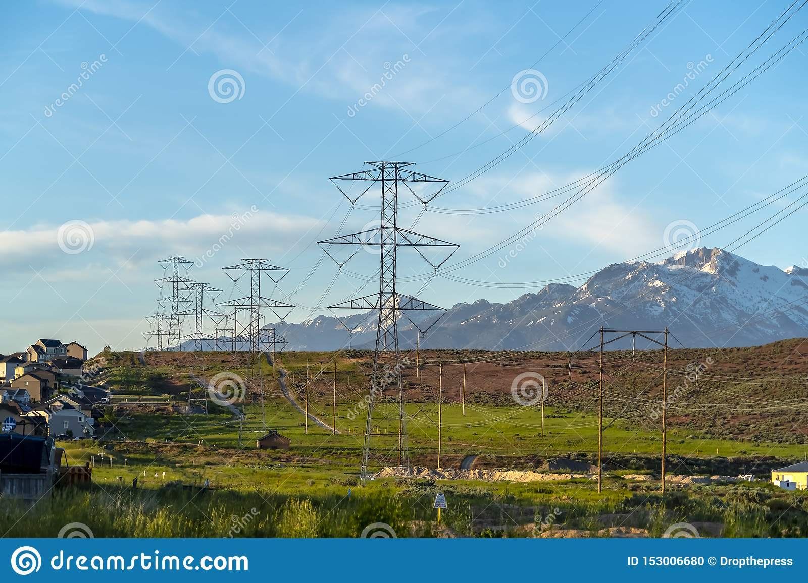 Power lines towering over neighborhood and roads in the valley on a sunny day