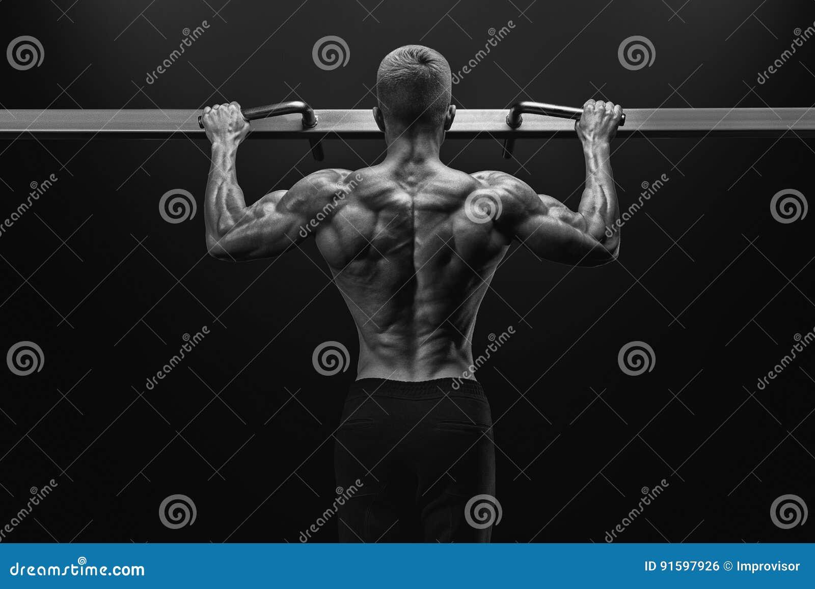 Power muscular bodybuilder guy doing pullups in gym. Fitness man