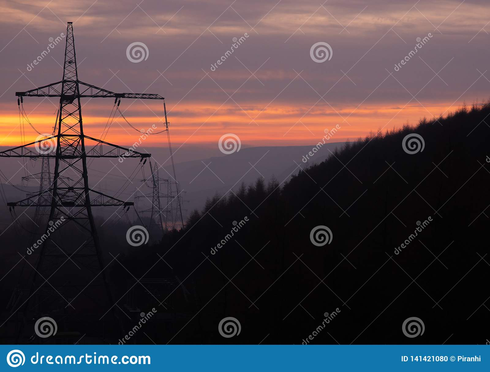 Power Pylons run through a forest at Sunset in the UK, Peak District