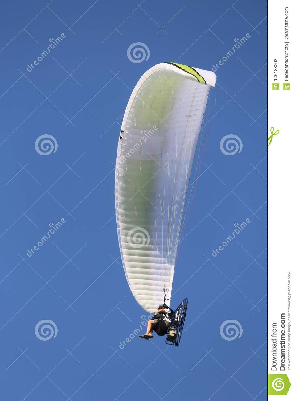 Powered Hang Glider Flies High In The Blue Sky With A Person Sit