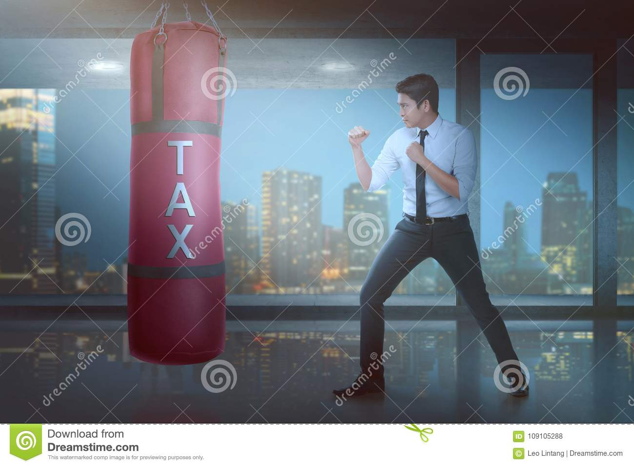 Powerful Asian Businessman Puncing Boxing Heavy Bag With Tax Sign On It In  The Office