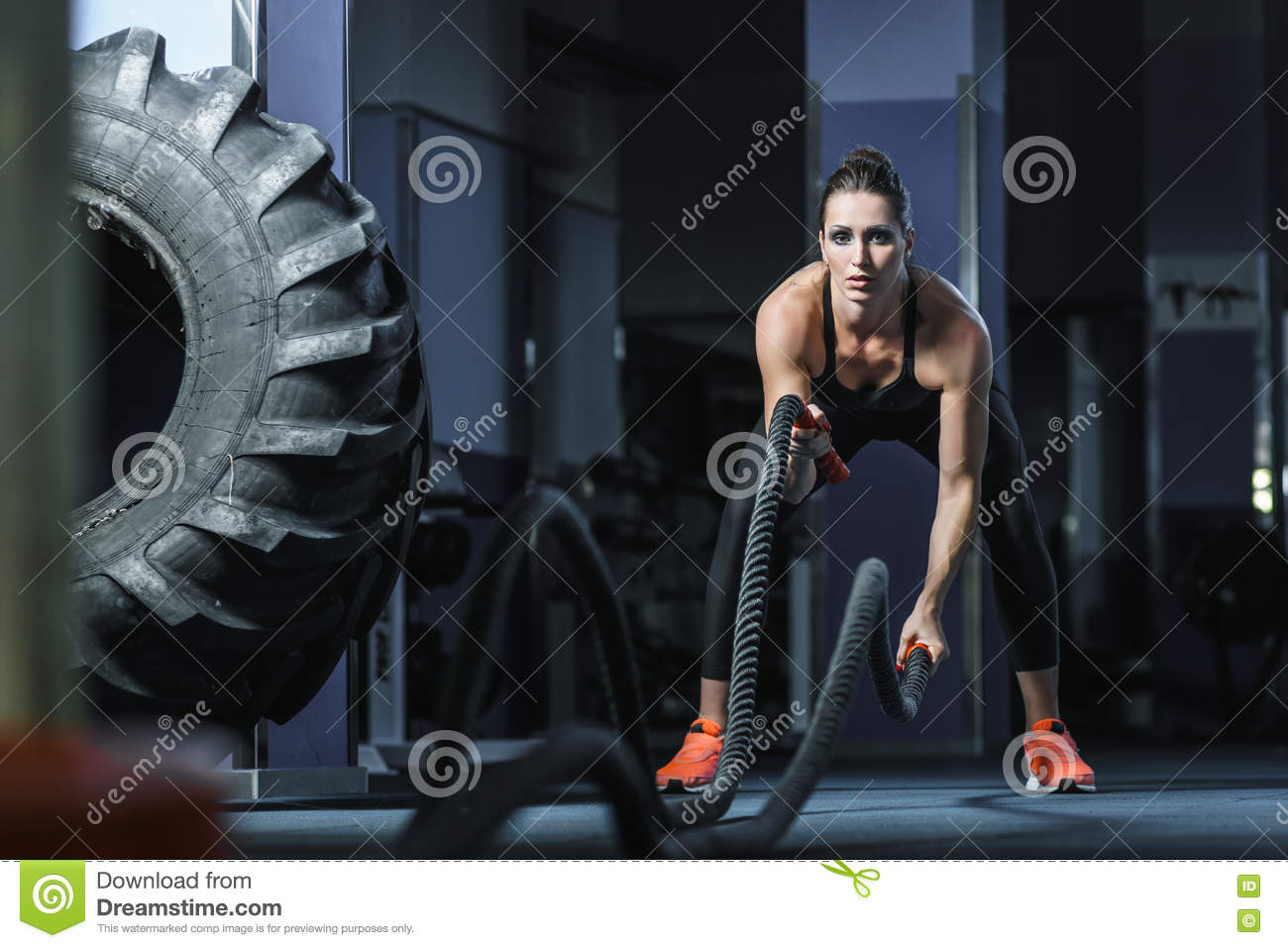 Powerful attractive muscular CrossFit trainer do battle workout with ropes