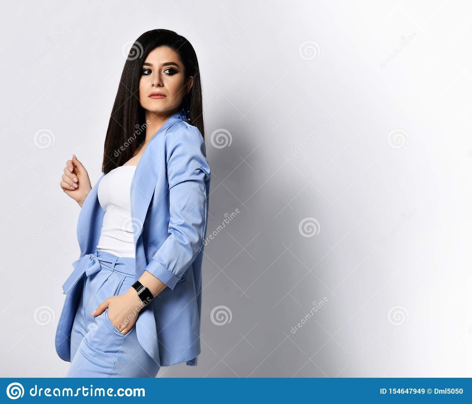 Powerful business woman in blue official suit turned back and looked over her shoulder at free text space on white