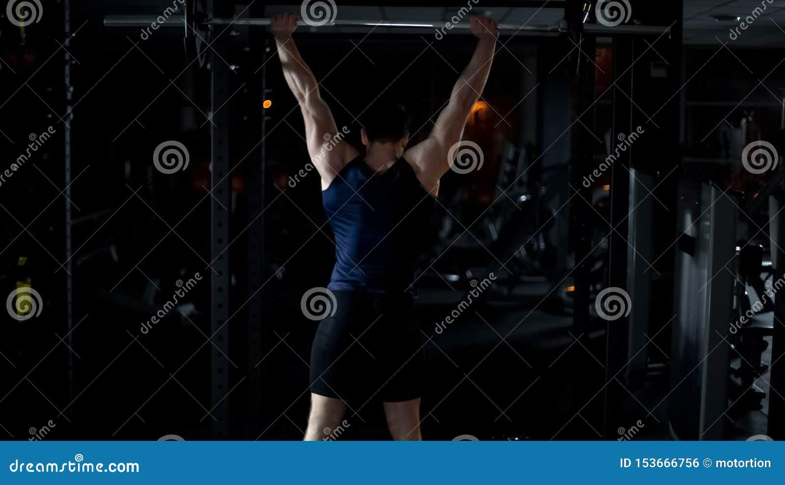 Powerlifter, das Übung mit Barbell, den Trainingsarmen und den Schultermuskeln tut