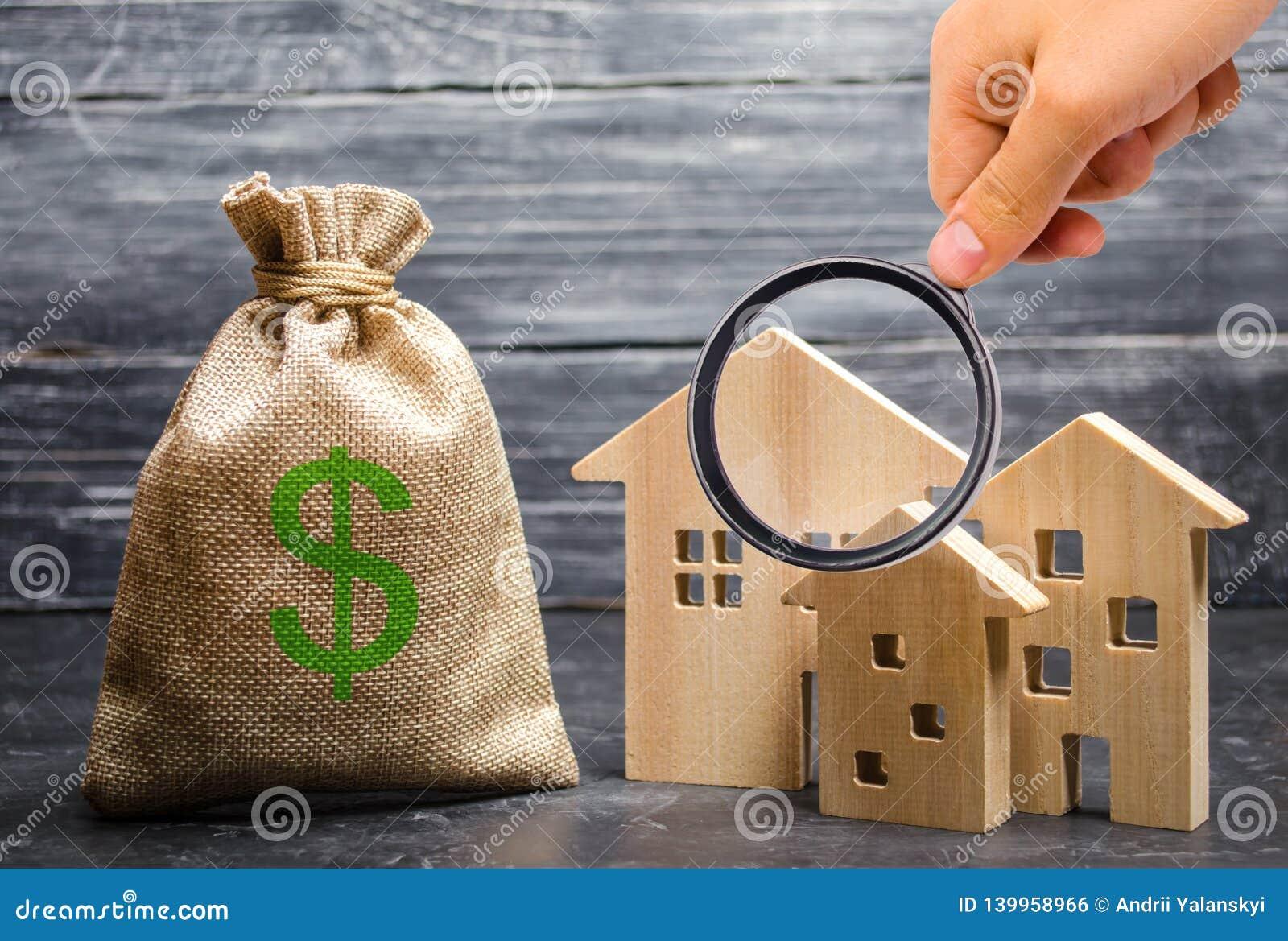 Powiększać - szkło jest przyglądający blisko torby z pieniądze trzy domu nieruchomości inwestycja i nabycie