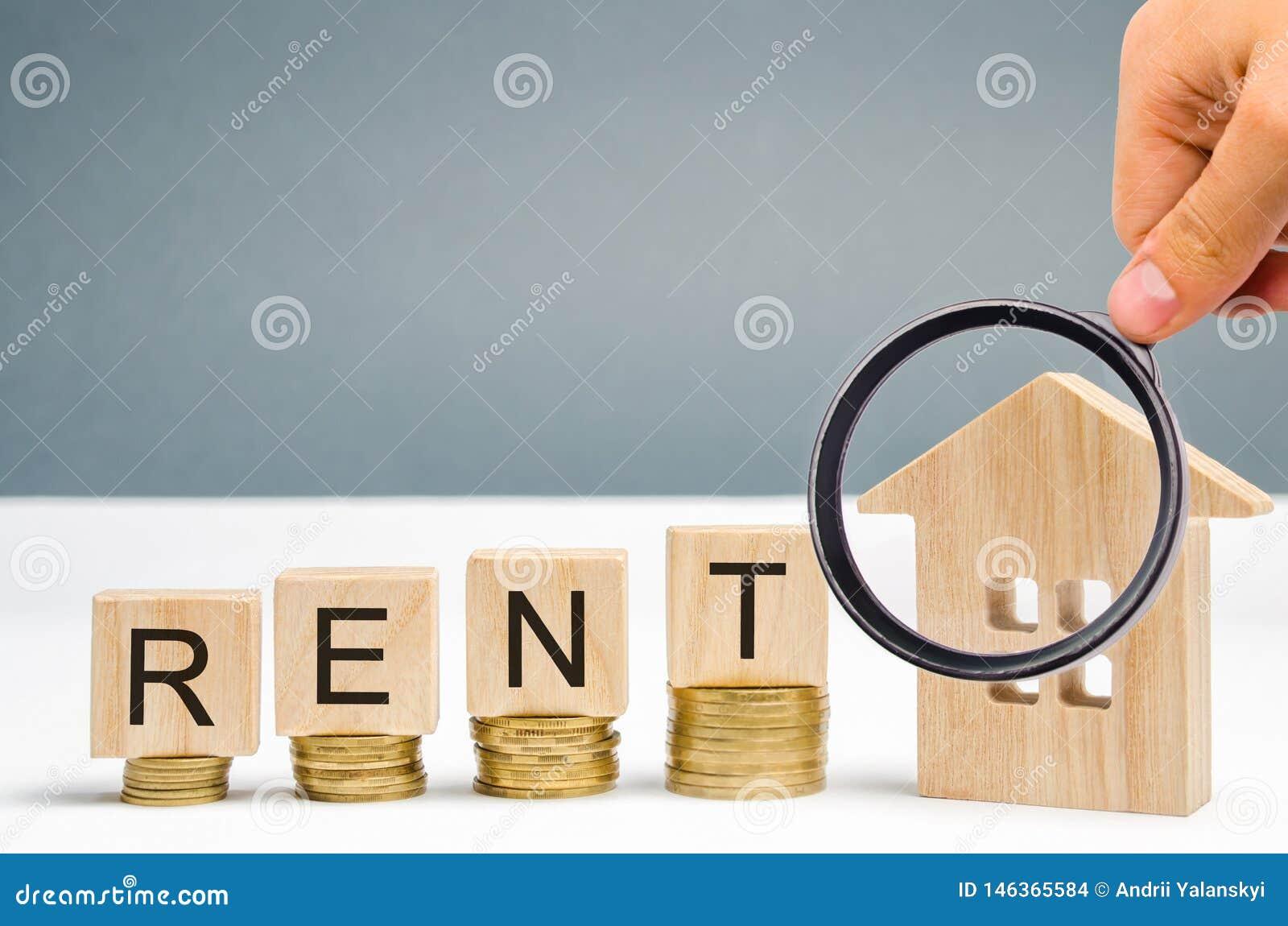 Powiększający - szkło, drewniani bloki z słowo czynszem, monety i miniaturyzuje dom Pojęcie wynajmowanie nieruchomość i budynek m