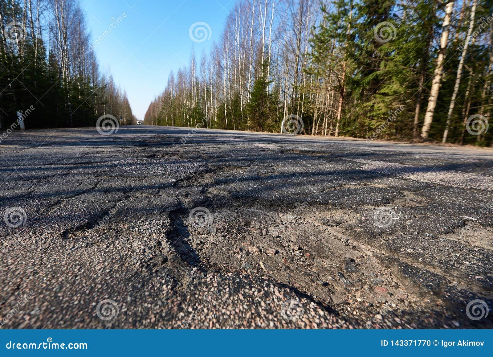 Powierzchnia autostrada iluminuje kosymi promieniami słońce Wielcy wyboje na drodze Narosły zagrożenia zagrożenie bieda