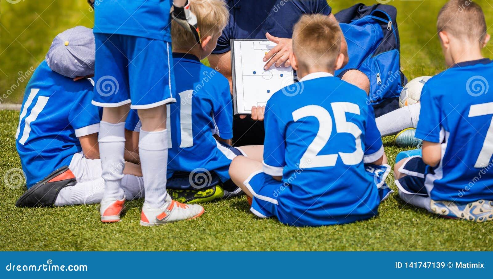 Powozowy trenowanie Żartuje piłki nożnej drużyny Młodości drużyna futbolowa z trenerem przy stadium piłkarski