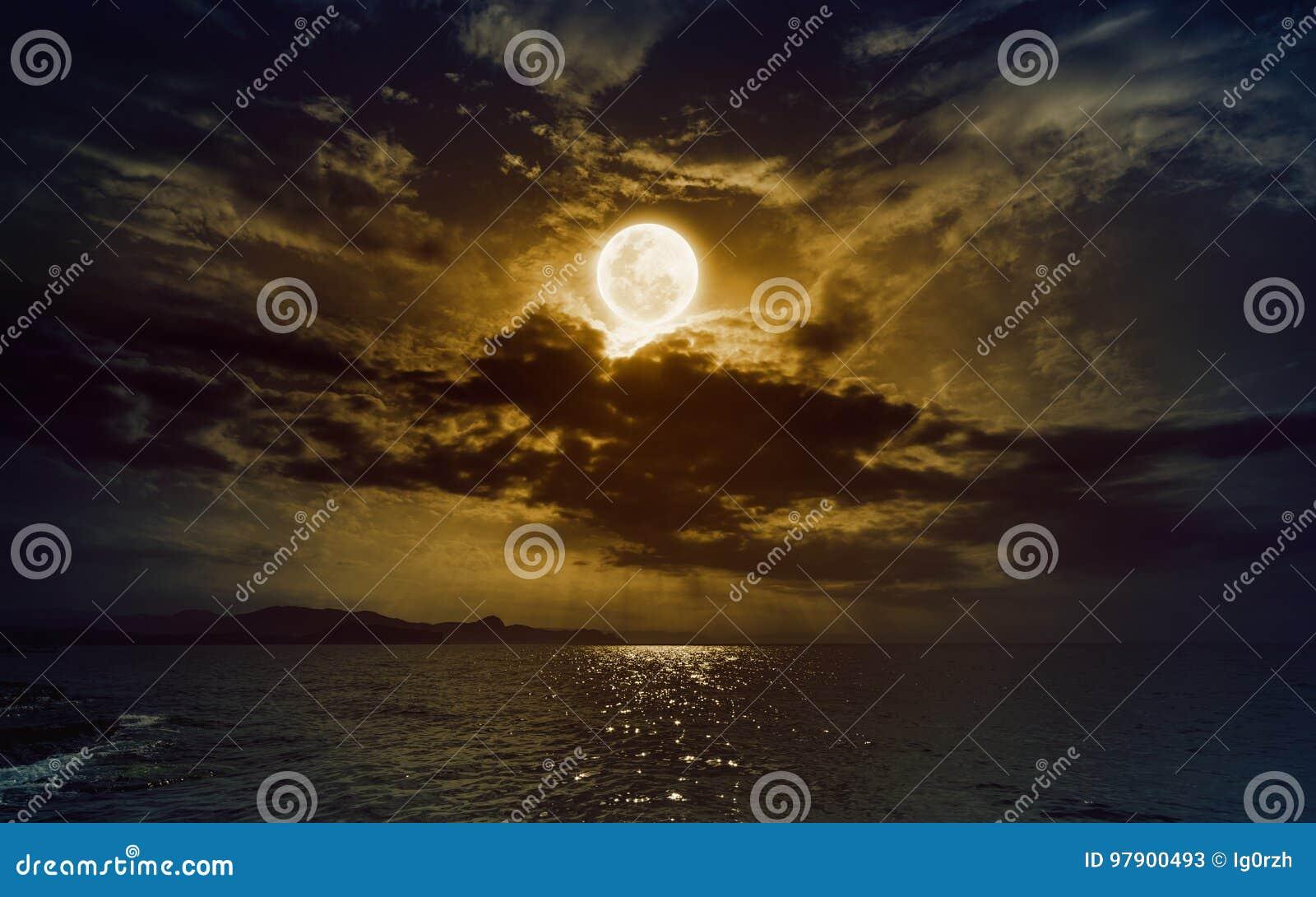 Powstający żółty księżyc w pełni w ciemnym nocnym niebie z odbiciem w wacie