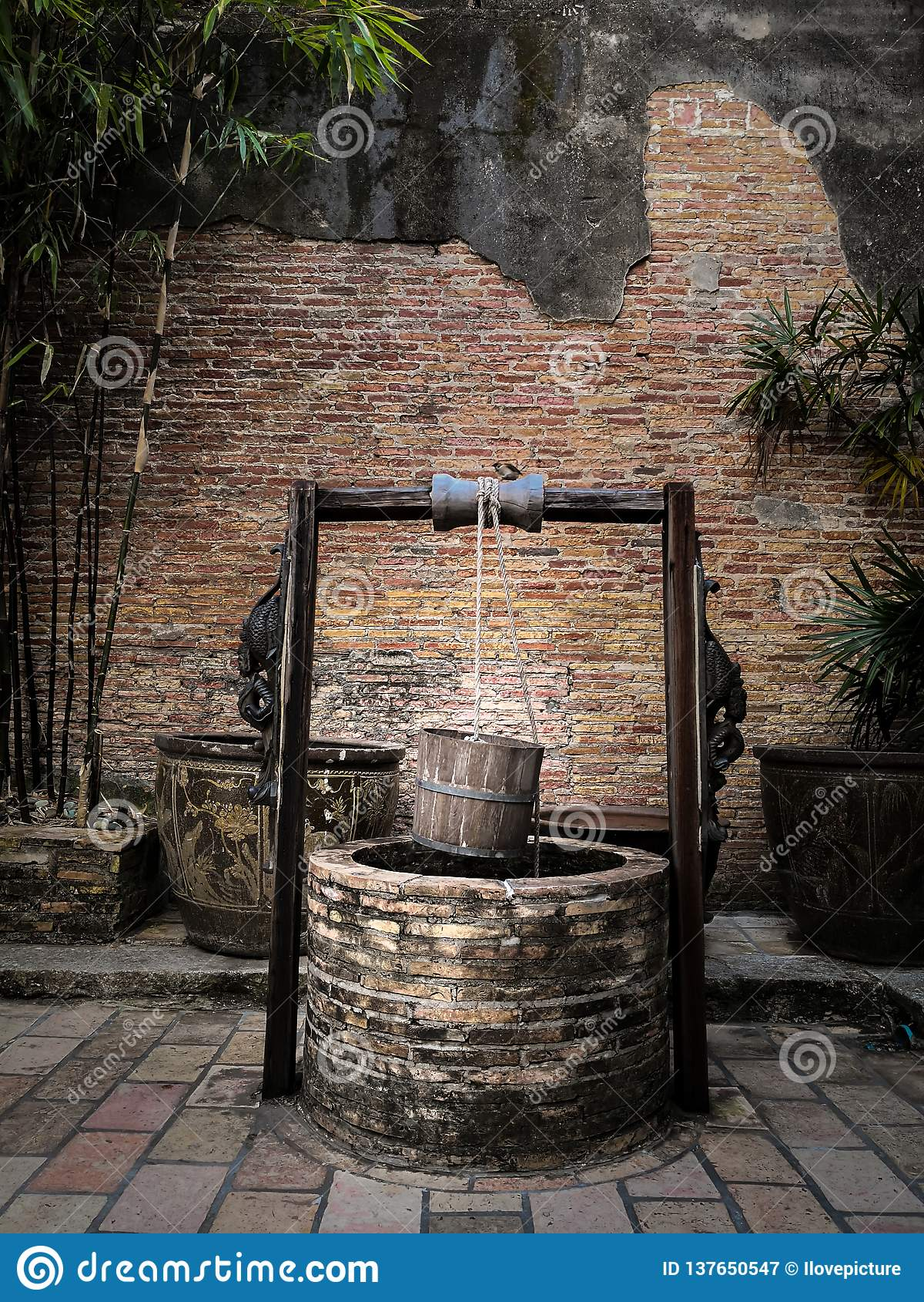 Pozo artesiano antiguo con el cubo de madera de la ejecución y el tejado de madera