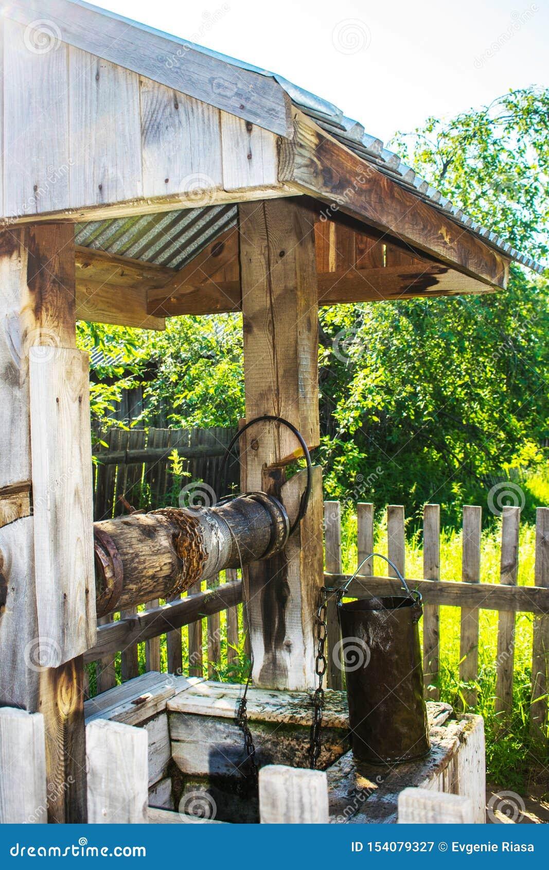 Pozo de madera r?stico viejo con el cubo Pueblo bien debajo del tejado con una cadena en un d?a nublado del oto?o, Rusia del meta