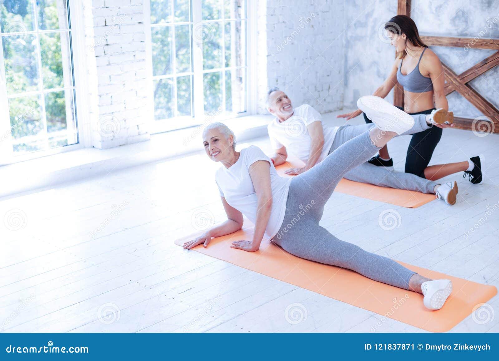 Pozytywna kobieta podnosi jej lewą nogę