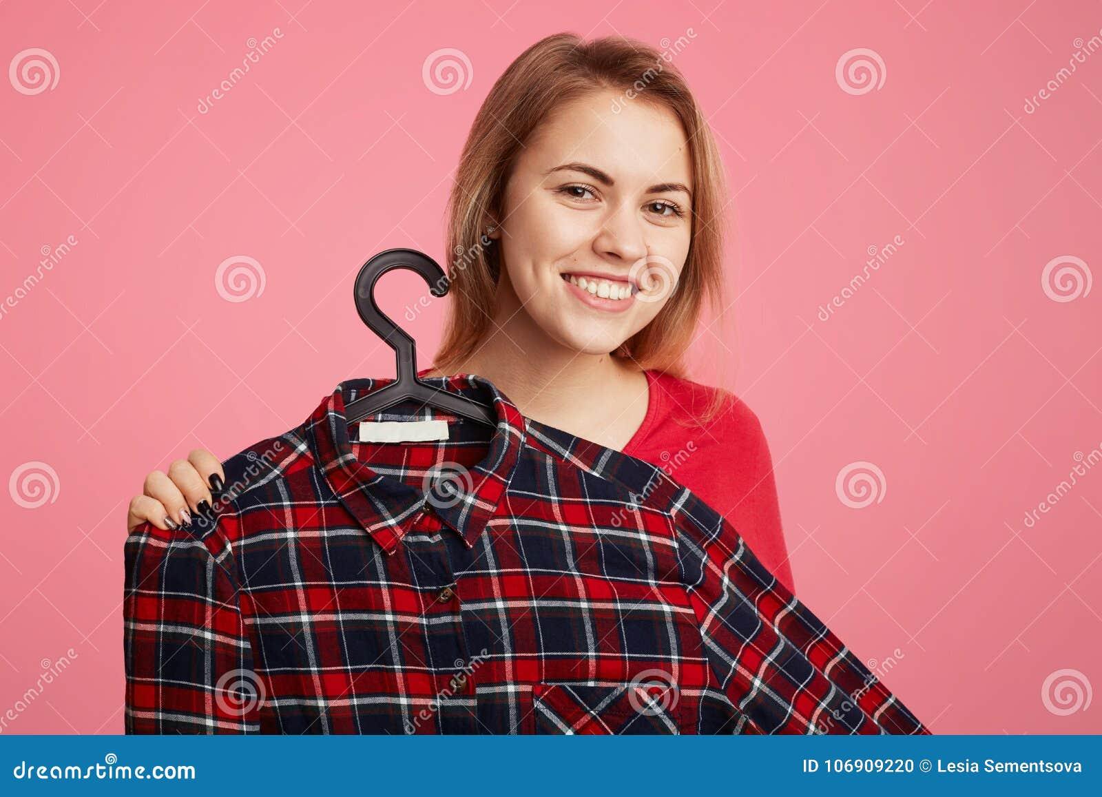 Pozytywna rozochocona młoda kobieta reklamuje modną w kratkę koszula na wieszakach, proponuje kupować je z niską ceną, sugeruje d