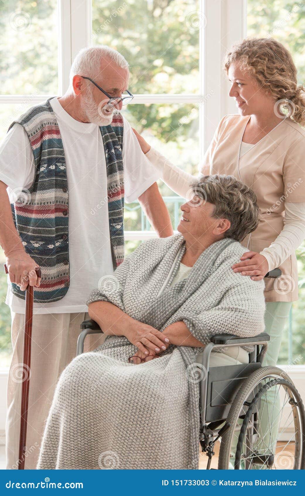Pozytywna starsza kobieta na wózku inwalidzkim z czułości pielęgniarką i starsza osoba przyjacielem z chodzącym kijem