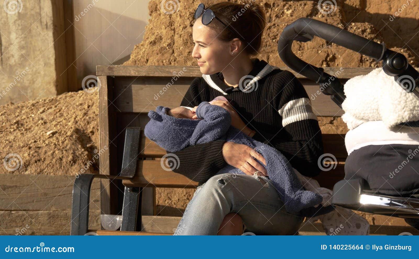 Pozytywnego i uśmiechniętego mama żywieniowy dziecko plenerowy na ławce ma odpoczynek