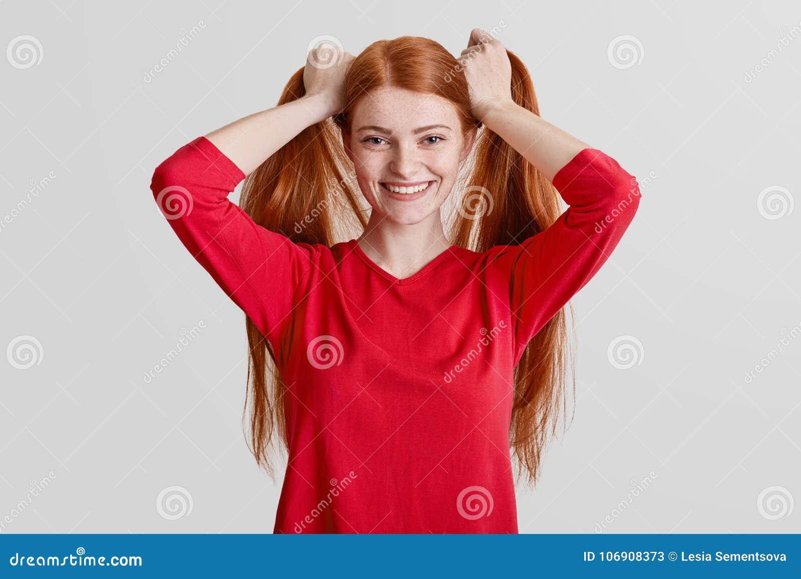 Pozytywnej rudzielec piegowata kobieta długie włosy, robi koników ogonom, zadawalający pozować przy kamerą, jest ubranym czerwone