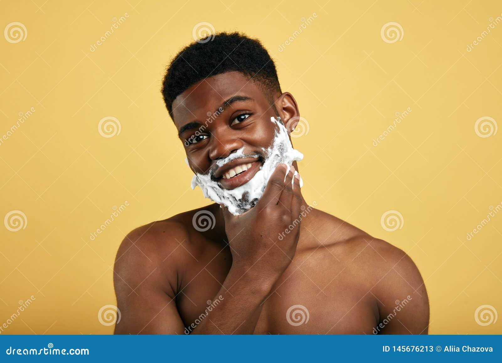 Pozytywny bez koszuli mężczyzna z golenie pianą ma prysznic, dotyka jego podbródek