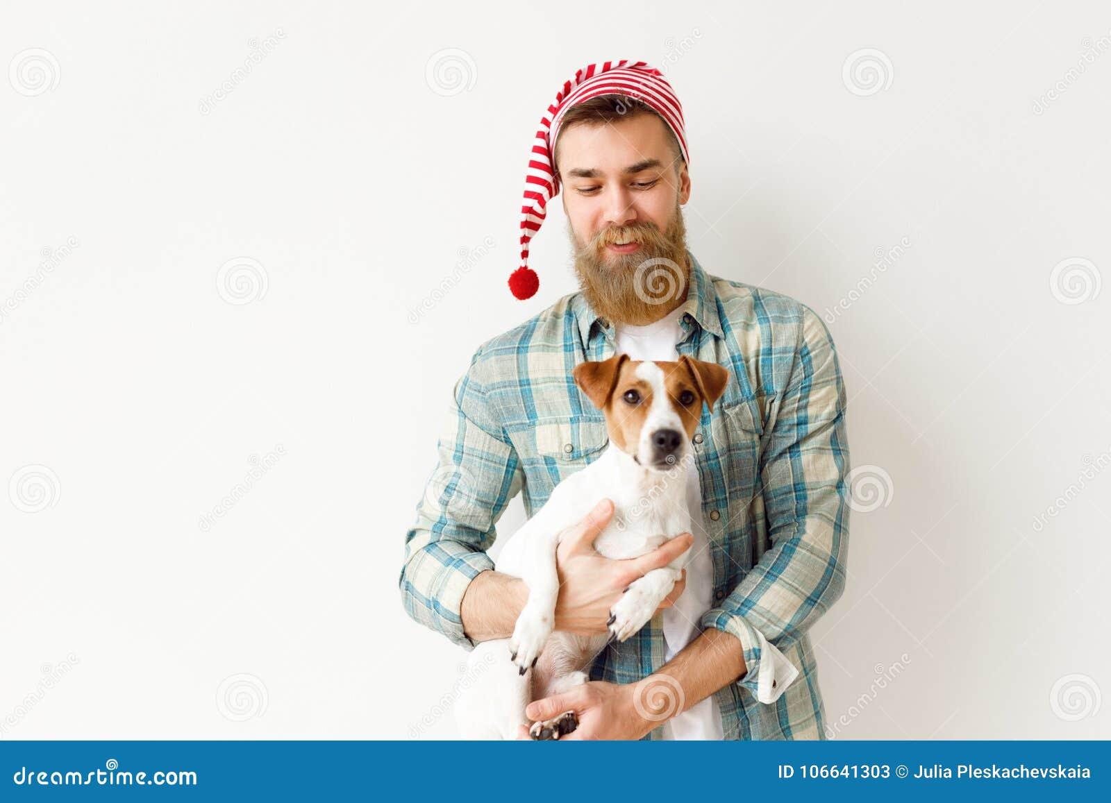 Pozytywny brodaty samiec model jest ubranym świątecznego kapelusz i w kratkę koszula, trzyma jego ulubionego zwierzęcia domowego