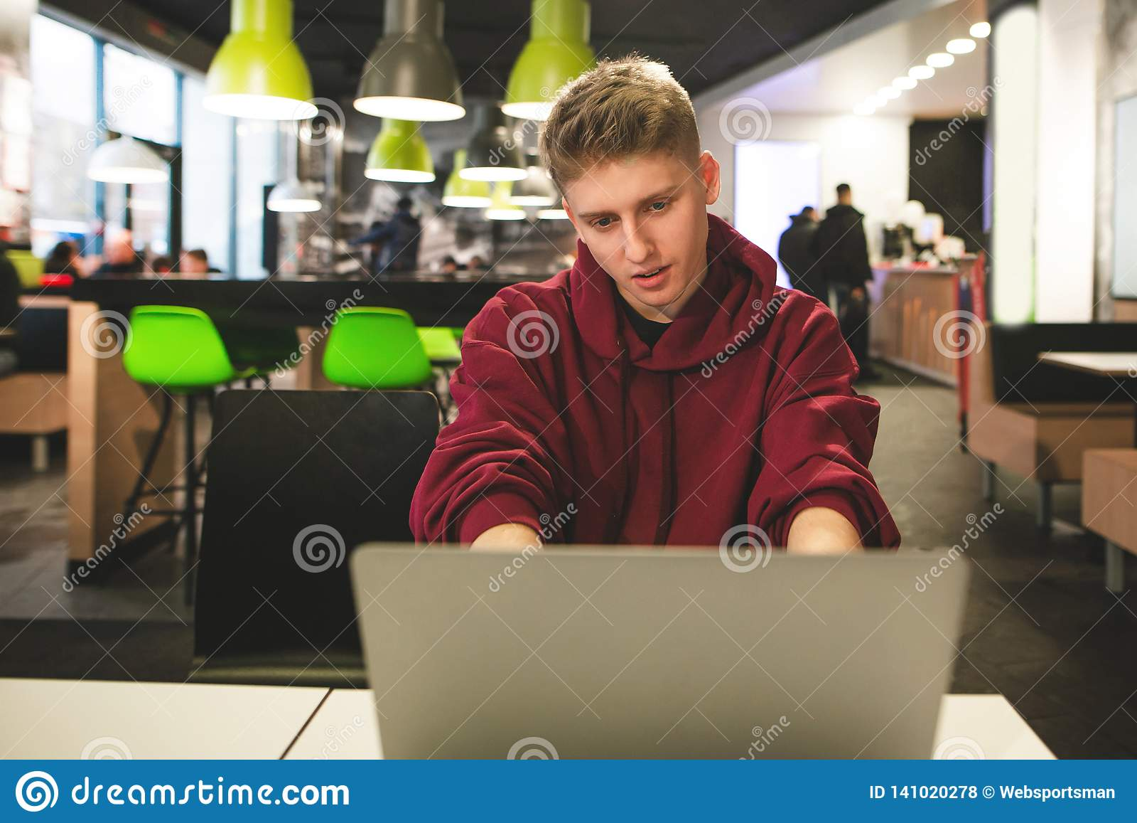 Pozytywny facet pracuje na laptopie na tle restauracja Szczęśliwe uczeń pracy