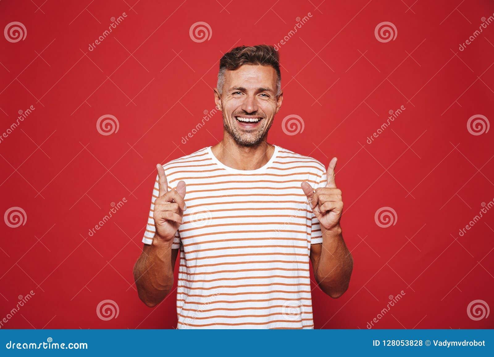 Pozytywny mężczyzna gestykuluje palce wskazujących oddolny a w pasiastej koszulce