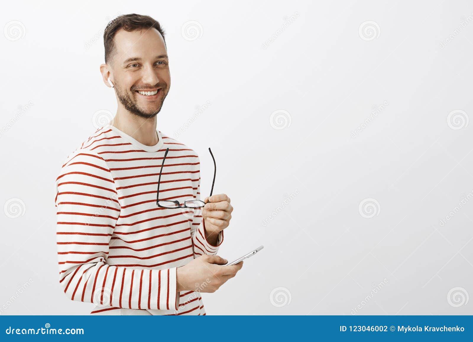 Pozytywny pomyślny męski biznesmen, brać daleko szkła, patrzeć na boku i ono uśmiecha się życzliwego, podnoszący muzykę słuchać w