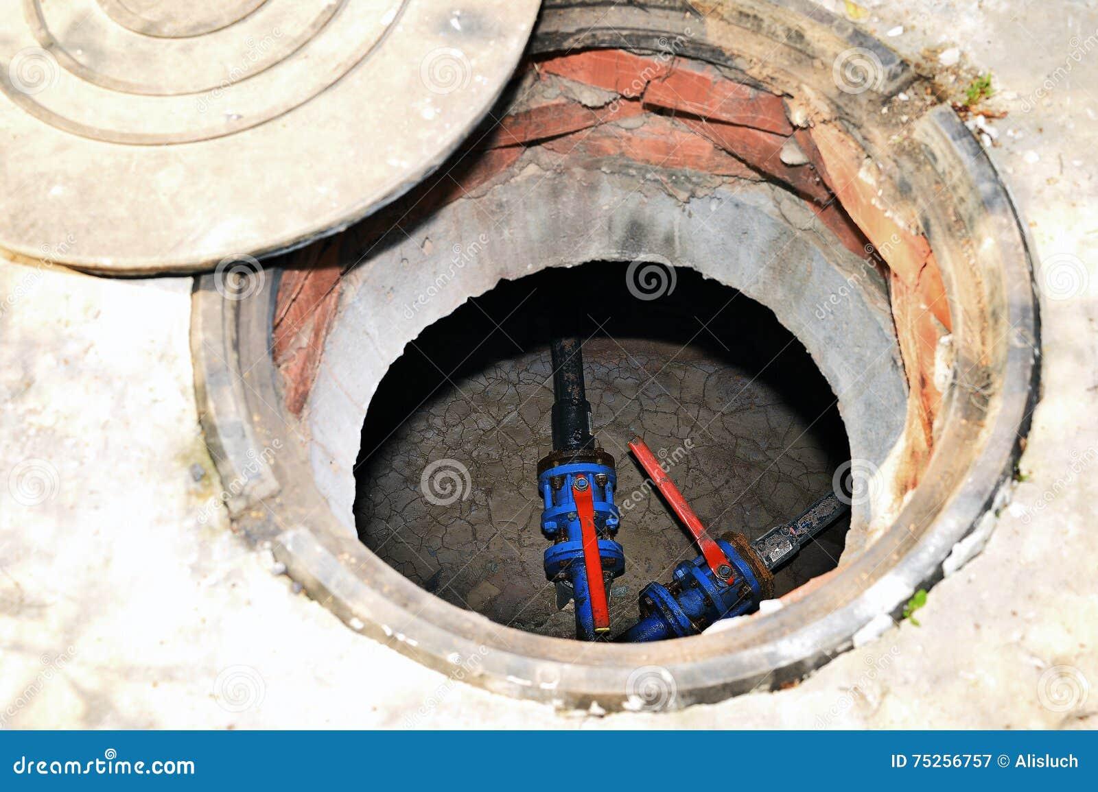 pozzo nero concreto con una covata aperta sulla terra di